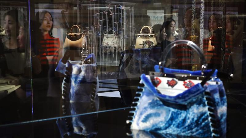 Women are reflected on glass panels as they look at specially made Italian luxury fashion brand handbags on display at an exhibition in Beijing.