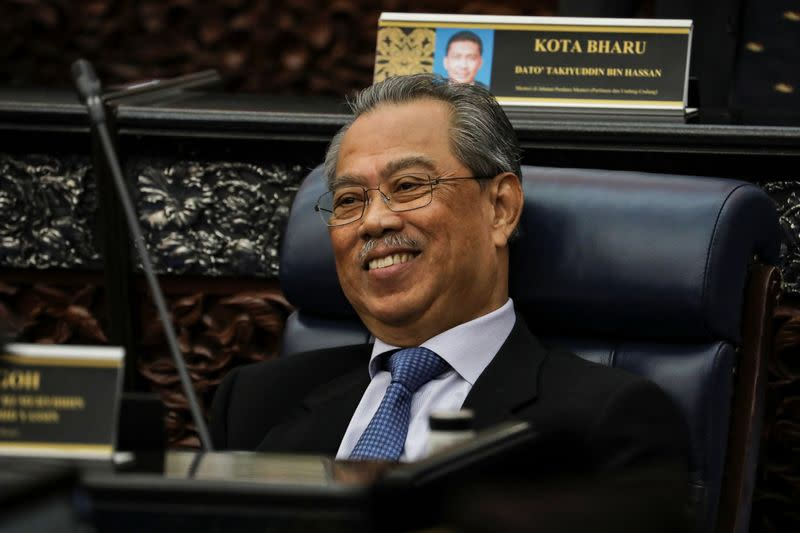 Malaysia's Prime Minister Muhyiddin Yassin smiles during a session of the lower house of parliament, in Kuala Lumpur