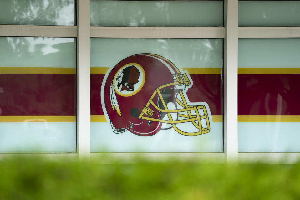"LANDOVER, MD - JULY 07: A Washington Redskins helmet logo adorns a window on the outside of FedEx Field on July 7, 2020 in Landover, Maryland. After receiving recent pressure from sponsors and retailers, the NFL franchise is considering a name change to replace Redskins. The term ""redskin"" is a dictionary-defined racial slur for Native Americans. (Photo by Drew Angerer/Getty Images)"