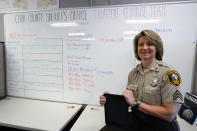 In this Friday, Aug. 13, 2021, photo Sheriff's Police Sgt. Bonnie Busching holds a tablet at the Cook County Sheriff's Office in Chicago. The Cook County Sheriff's Office has started putting people having a crisis face to face with mental health professionals before they lash out at deputies or try to harm themselves and to do it they're taking a page out of countless businesses forced hold their meeting virtually. (AP Photo/Nam Y. Huh)