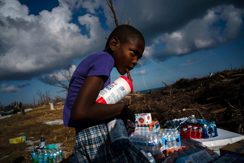 Ayfon Minus, 8, collects donated food that was brought by helicopter from Freeport to the Hurricane Dorian destroyed village of High Rock, Grand Bahama, Bahamas, Sept. 10, 2019. | Ramon Espinosa—AP