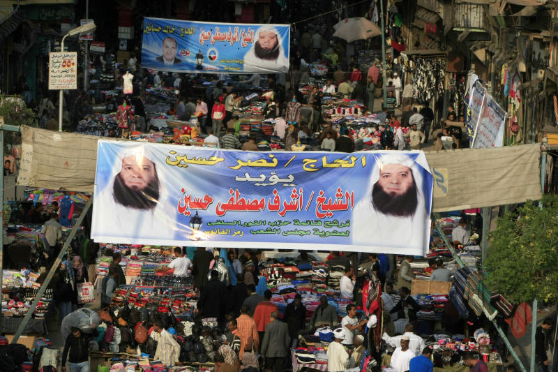 """FILE - In this Friday, Nov. 25, 2011 photo, Egyptians crowd at a popular market under Arabic banners supporting Ashraf Mustafa Hussein, a Salafi candidate to the parliamentary elections, in Cairo, Egypt. Egypt's largest ultraconservative Islamist party, which has emerged as a potent political force in the country, elected a new leader on Wednesday after the previous head with dozens of other members broke away to form their own political group following months of infighting. Arabic on the banners read """"Sheikh Ashraf Mustafa Hussein, candidate of the Salafi Al-Nour party."""" (AP Photo/Amr Nabil, file)"""