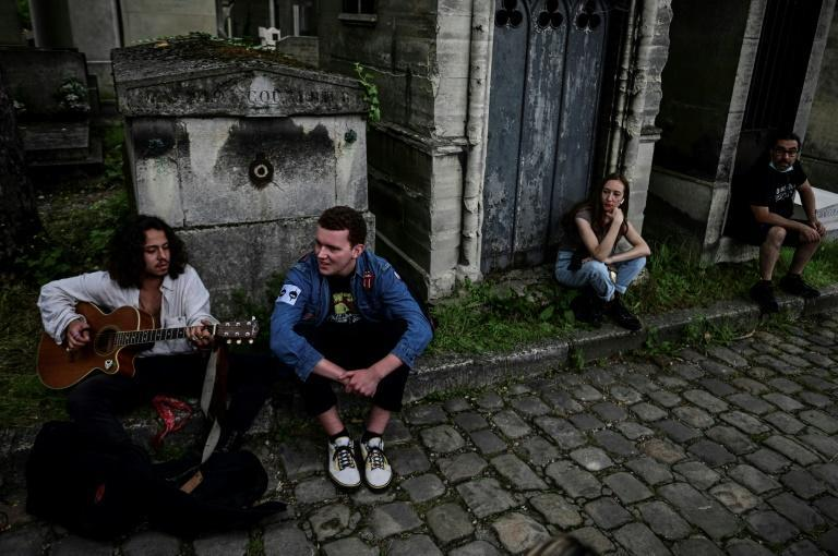 Marius de la Brosse (L) whipped out his guitar to entertain other fans gathered at the grave