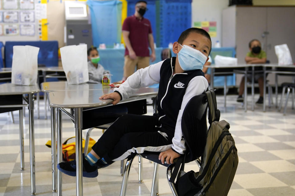A summer school student wears a protective mask in class at the E.N. White School in Holyoke, Mass., on Wednesday, Aug. 4, 2021. Schools across the U.S. are about to start a new year amid a flood of federal money larger than they've ever seen before, an infusion of pandemic relief aid that is four times the amount the U.S. Department of Education sends to K-12 schools in a typical year. (AP Photo/Charles Krupa)