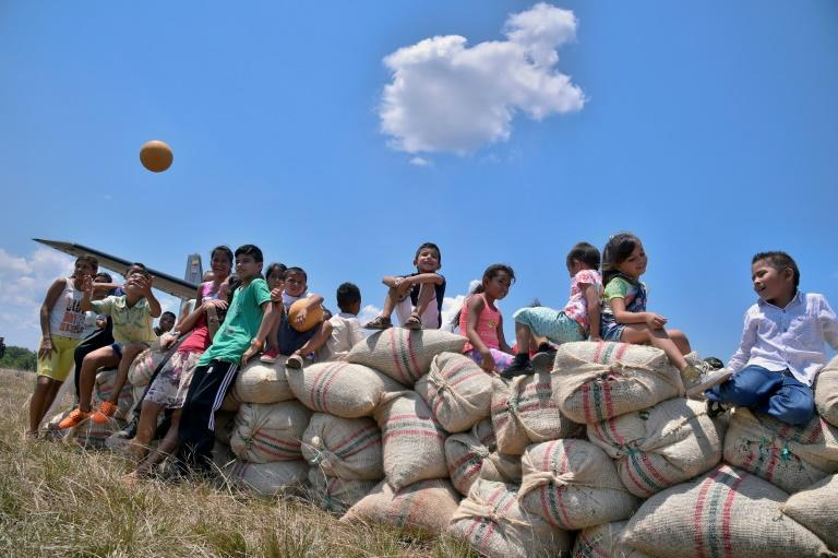 Children sit on sacks of cocoa beans set to be loaded onto a Colombian Air Force plane at the Guerima village airstrip in the municipality of Cumaribo, Vichada department, eastern Colombia, on February 16, 2017