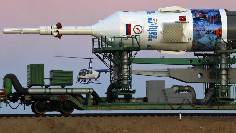 A Russian police helicopter guards the Russia's booster rocket Soyuz-FG with the space capsule Soyuz TMA-11M that will carry new crew to the International Space Station (ISS) as the rocket is transported from hangar to the launch pad at the Russian leased Baikonur cosmodrome, Kazakhstan, Tuesday, Nov. 5, 2013. The rocket is emblazoned with the emblem of the Winter Olympics in Sochi. For the first time, it will also carry an Olympic torch to space as part of the ongoing Olympic torch relay. The torch will be brought back along with the station's current crew. The rocket is scheduled to blast off on Thursday, Nov. 7. (AP Photo/Dmitry Lovetsky)