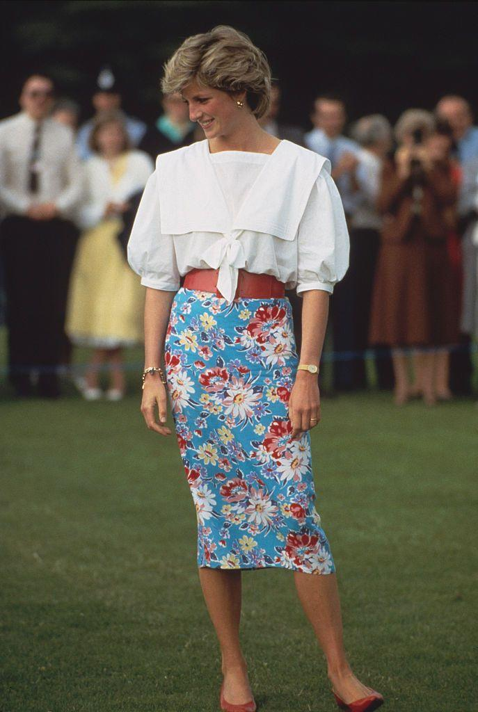 """<p>Diana belted a shin-length pencil skirt, and paired it with a <a href=""""https://www.townandcountrymag.com/style/fashion-trends/g35843582/big-collar-shirts-fashion-trend/"""" rel=""""nofollow noopener"""" target=""""_blank"""" data-ylk=""""slk:collared sailor blouse"""" class=""""link rapid-noclick-resp"""">collared sailor blouse</a> to a polo match in Cirencester in June 1985. </p>"""