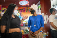 Rep. Ilhan Omar, center, D-Minn., talks with Dulce Sanchez, whose family owns Dulceria La Piñata at Mercado Central in Minneapolis, on Tuesday, Aug. 11, 2020, primary day in the state. Omar faces Antone Melton-Meaux in the Democratic primary, (Leila Navidi/Star Tribune via AP)