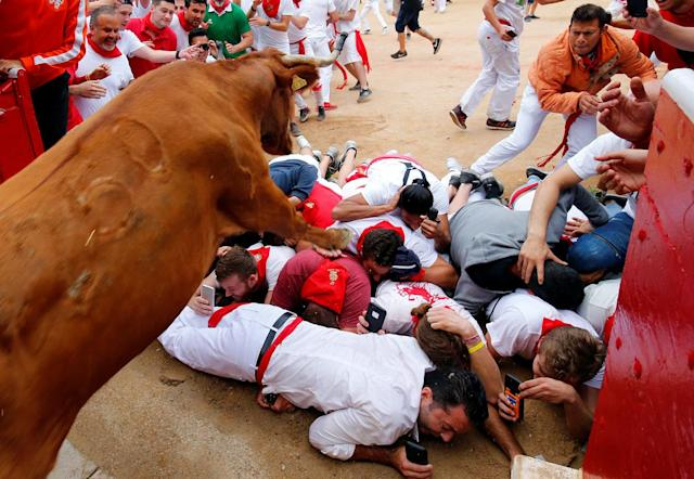 <p>A wild cow leaps over revellers as it enters the bullring following the seventh running of the bulls at the San Fermin festival in Pamplona, northern Spain, July 13, 2017. (Photo: Susana Vera/Reuters) </p>