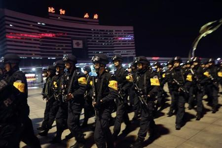 Police carrying guns walk along a street during a drill against emergency terror incidents in Shenyang