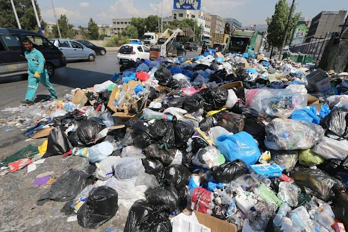Garbage collectors remove waste from a street in Beirut's eastern suburb of Dora to a temporary location outside of the Lebanese capital on August 31, 2015 (AFP Photo/Joseph Eid)