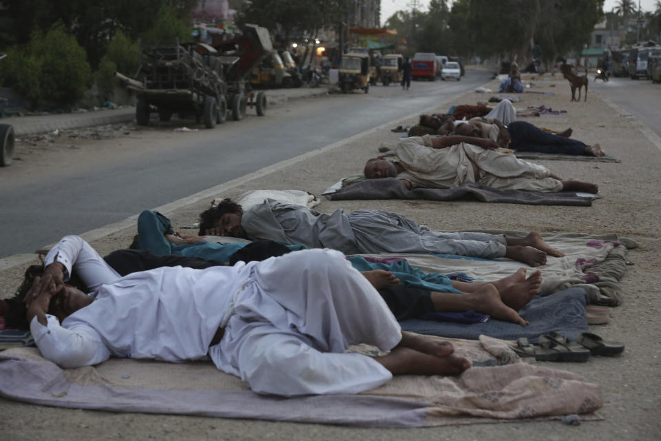 FILE - In this Thursday, June 18, 2020 file photo, vendors and rickshaw drivers sleep in the open early on a hot summer morning in Karachi, Pakistan, as parts of the country continued to experience an intense heat wave. (AP Photo/Fareed Khan)