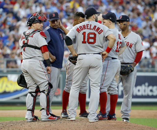 Boston Red Sox manager Alex Cora talks to his players on the mound while making a pitching change during the fifth inning of the team's baseball game against the Kansas City Royals on Saturday, July 7, 2018, in Kansas City, Mo. (AP Photo/Charlie Riedel)
