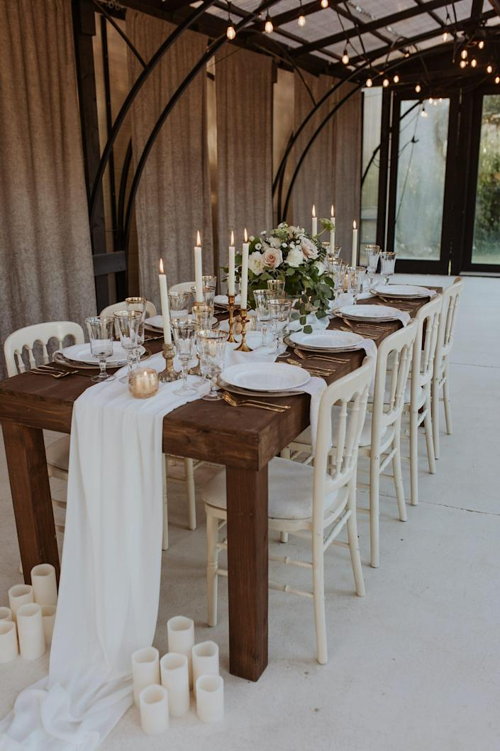 A table with a white runner, candles, and white and gold plates in a room covered in windows.