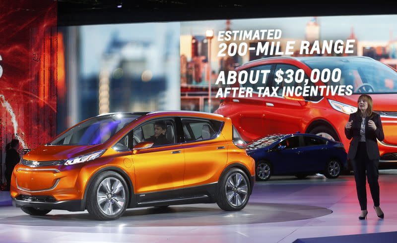 General Motors CEO Mary Barra speaks next to the Chevrolet Bolt EV electric concept car and the 2016 Chevrolet Volt hybrid after they were unveiled during the first press preview day of the North American International Auto Show in Detroit