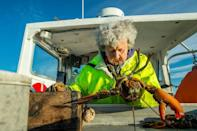 Wearing wellies, slickers and rubber gloves, Oliver stands over the holding tank and grabs lobsters to inspect one at a time as her son passes them to her