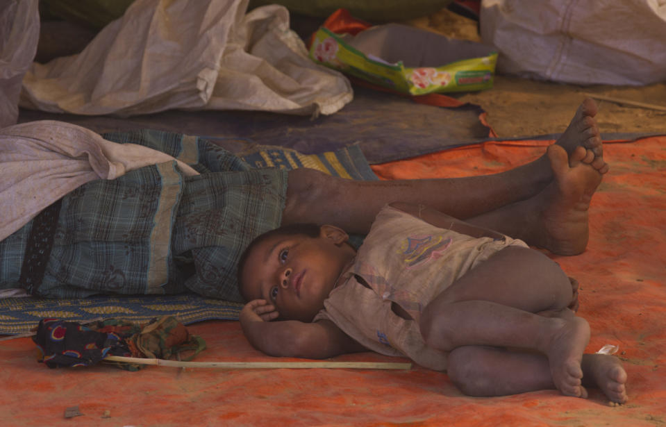 In this Thursday, Jan. 18, 2018, file photo, a newly arrived Rohingya family rests under a temporary shelter at Balukhali refugee camp near Cox's Bazar, Bangladesh. United Nations agencies are warning that more than 350 million people in the Asia-Pacific are going hungry as the coronavirus pandemic destroys jobs and pushes food prices higher. (AP Photo/Manish Swarup, File)