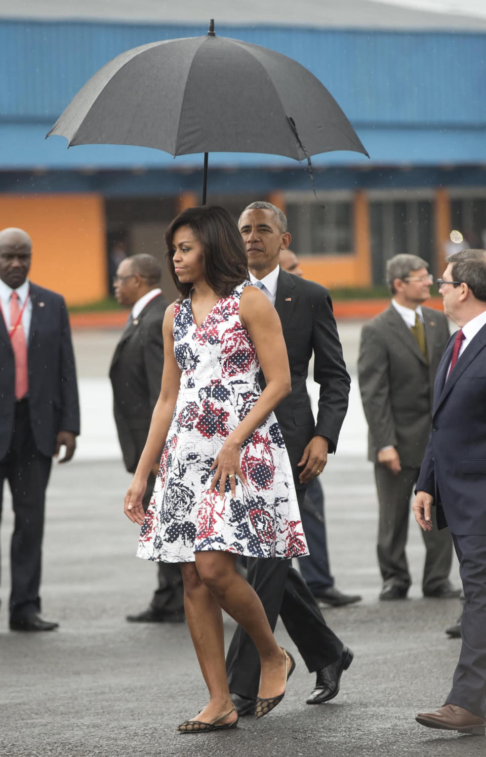 <p>For the first time in nine decades, an American president and his family are visiting Cuba. The Obamas probably expected to be greeted with sunshine, so they dressed for the tropical climate. Instead, it was pouring rain and the first lady's floral dress from Carolina Herrera wasn't weather appropriate. Luckily, she had her chivalrous husband to protect her from the storm. <i>Photo: AP</i></p>