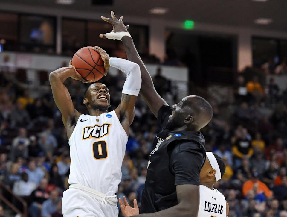 VCU's De'Riante Jenkins (0) is fouled by Central Florida's Tacko Fall, right, during the first half of a first-round game in the NCAA men's college basketball tournament Friday, March 22, 2019, in Columbia, S.C. (AP Photo/Richard Shiro)