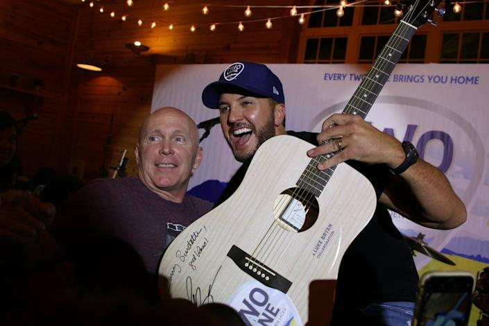 Luke Bryan poses with the winner of an auction for a signed guitar during the event on Tuesday evening. The sale price was $1,500, with all proceeds going to the Brett Boyer Foundation.