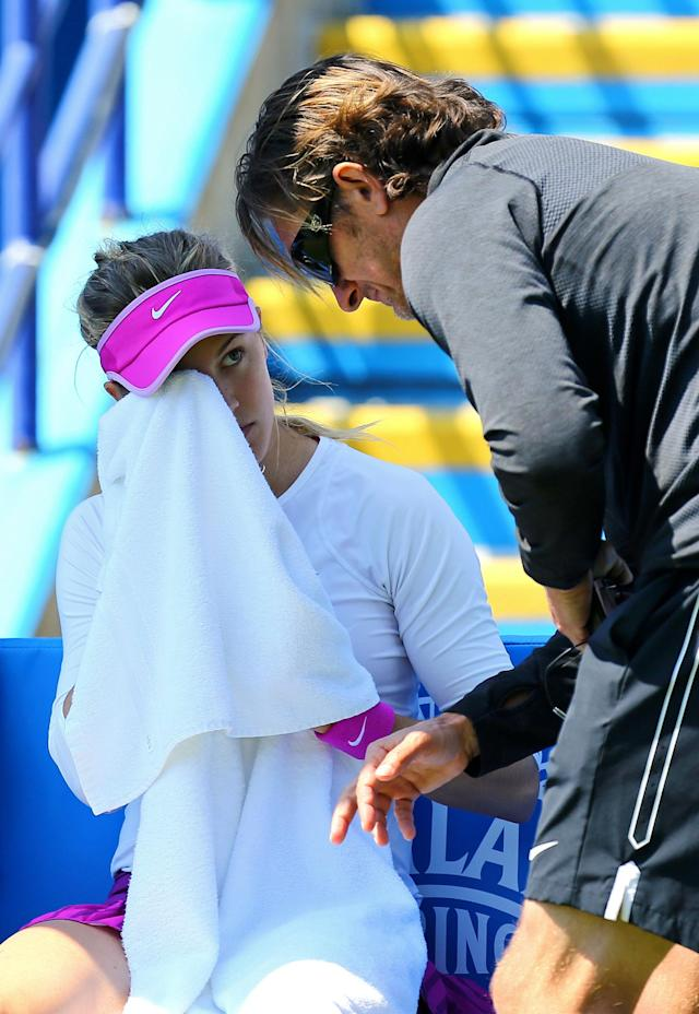 Canada's Eugenie Bouchard takes advice from her coach before retiring in her match against Switzerland's Belinda Bencic during day five of the women's international tennis tournament at Devonshire Park, Eastbourne, England, Wednesday June 24, 2015. (Gareth Fuller/PA via AP) UNITED KINGDOM OUT NO SALES NO ARCHIVE