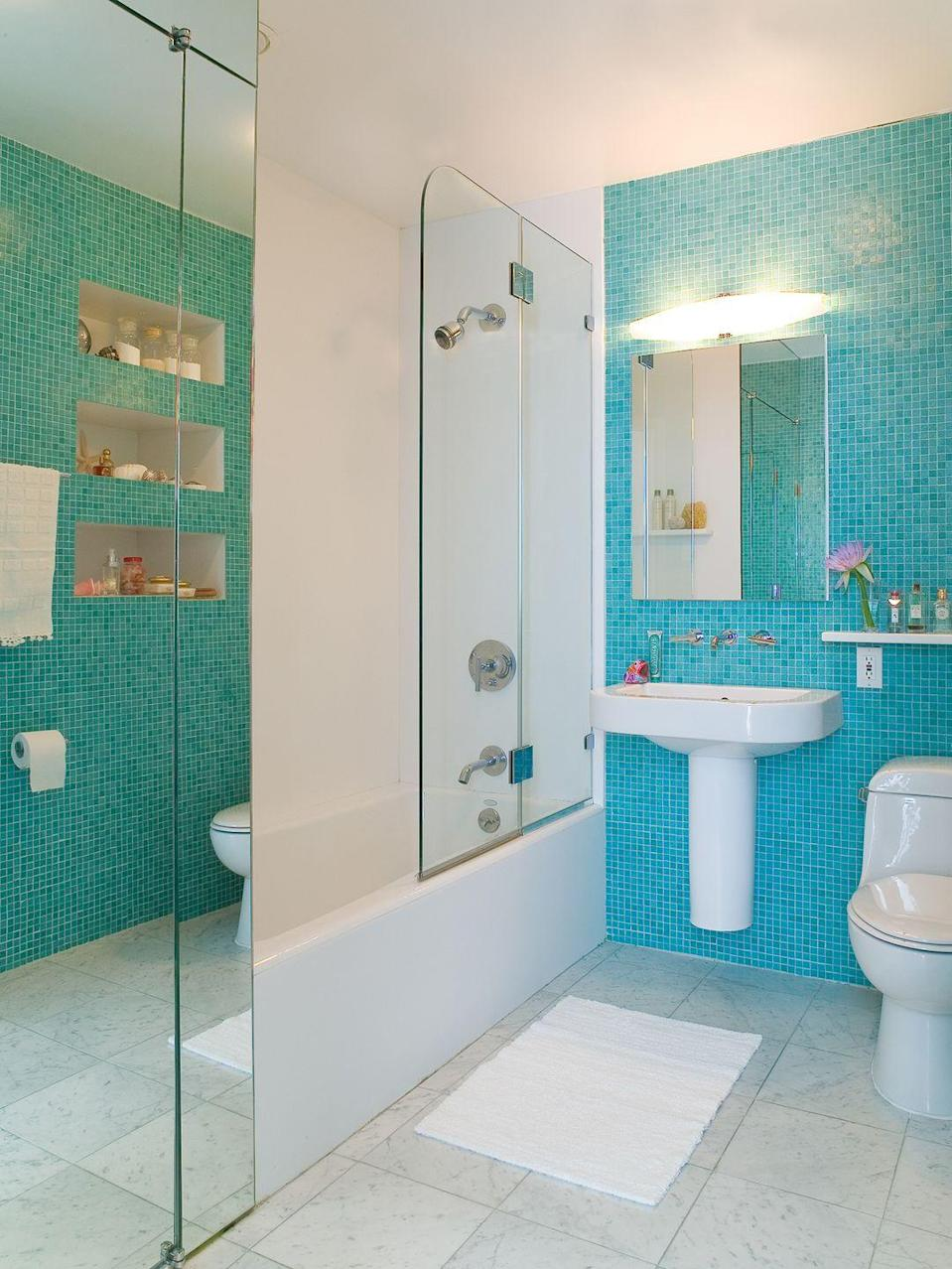 <p>An accent wall of small turquoise tiles adds a jolt of personality to this bathroom setup.</p>