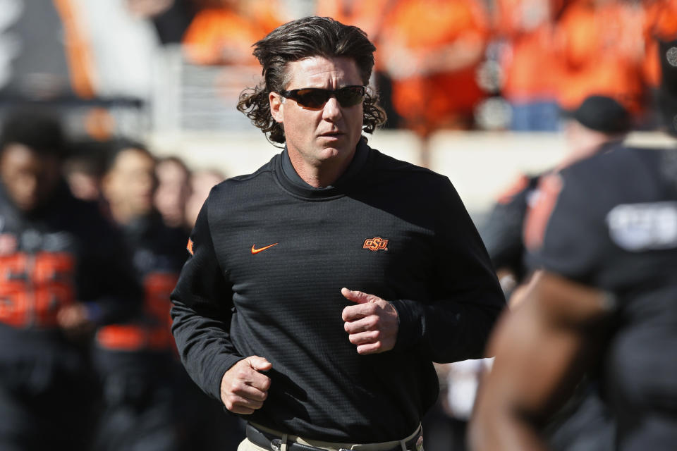 FILE - In this Nov. 2, 2019, file photo, Oklahoma State coach Mike Gundy runs onto the field before the team's NCAA college football game against TCU in Stillwater, Okla. Hubbard said on Twitter that he wont do anything with the program until there is change after Gundy was photographed wearing a T-shirt representing far-right online publication One America News Network. Gundy is seen in a photograph on Twitter wearing the T-shirt with the letters OAN. (AP Photo/Sue Ogrocki, File)