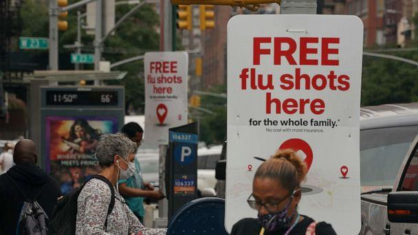 PHOTO: People walk past free flu shot advertisements outside of drugstores on Aug. 19, 2020, in New York. (Bryan R. Smith/AFP via Getty Images)
