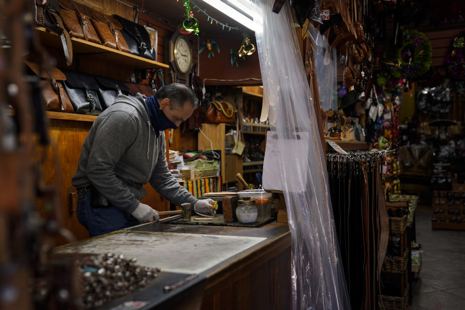 Leather artisan Armando Murillo works in his shop on Olvera Street in downtown Los Angeles, Wednesday, Dec. 16, 2020. Olvera Street, known as the birthplace of Los Angeles, has been particularly hard hit by the coronavirus pandemic, with shops and restaurants closed and others barely hanging on. Only a handful of businesses remain open on weekdays as tourism has cratered and downtown offices are closed and festive events held throughout the year have been canceled. (AP Photo/Jae C. Hong)