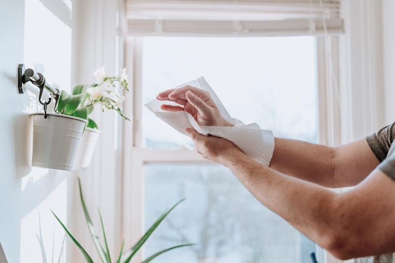 Person drying hands with paper towels to prevent disease dissemination, Covid-19