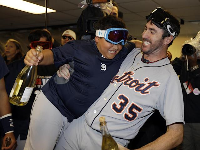 Detroit Tigers pitcher Justin Verlander (35) picks up Victor Martinez, Jr., son of Tigers' Victor Martinez, in the locker room as they celebrate their 3-0 win over the Oakland Athletics in Game 5 of an American League baseball division series in Oakland, Calif., Thursday, Oct. 10, 2013. (AP Photo/Ben Margot)