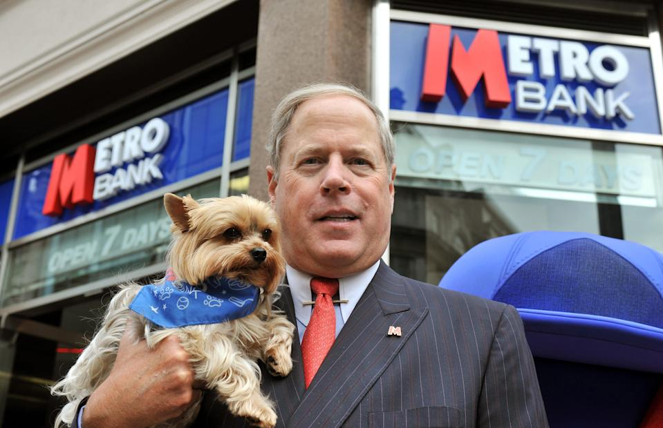 RETRANSMITTED WITH ADDITIONAL CAPTION INFORMATION. ADDING DOG'S NAME Founder and Vice Chairman  Vernon Hill II with his dog Duffy, outside the newly opened Metro Bank branch in Holborn, central London. The first high street bank to launch in the UK for more than 100 years opened its doors to customers today but its products received a lukewarm response from industry commentators.   (Photo by John Stillwell/PA Images via Getty Images)