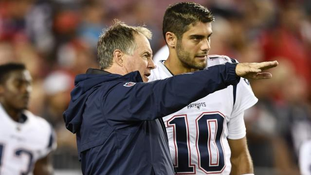 Patriots head coach Bill Belichick speaks to quarterback Jimmy Garoppolo before a game in October. (Getty)