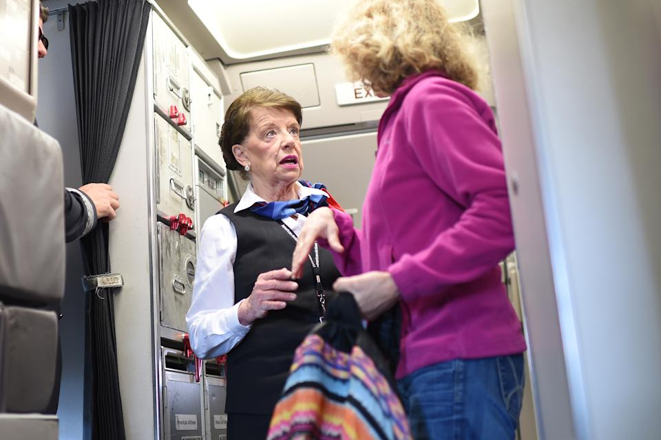 An American Airlines flight attendant greets passengers disembarking from her daily return flight to Boston at Ronald Reagan Washington Airport in Arlington, Virginia on December 19, 2017. (Photo credit should read ERIC BARADAT/AFP via Getty Images)