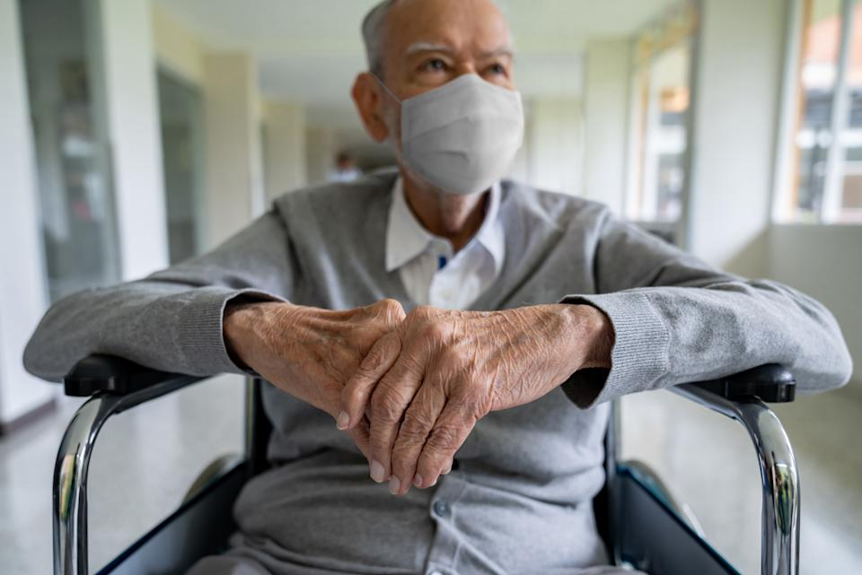 Senior adult in a wheelchair at the hospital wearing a facemask to avoid coronavirus – pandemic lifestyle concepts