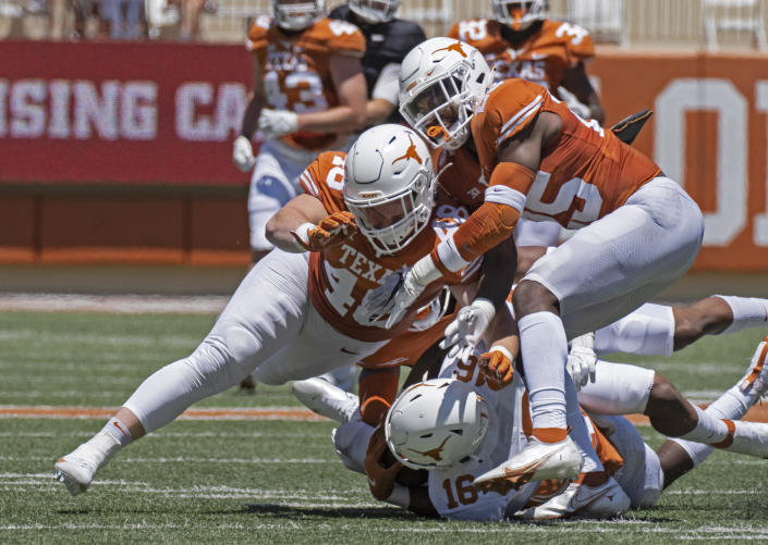 April 24, 2021 file photo shows Texas defenders Jake Ehlinger, left, and B.J. Foster, right, tackling Kayvontay Dixon (16) during the first half of the Orange and White spring scrimmage college football game in Austin, Texas. / Credit: Michael Thomas / AP