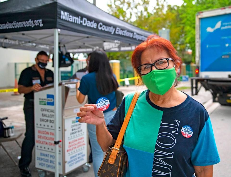 Miami-Dede resident Zaida Perez shows her sticker after casting her vote on first day of early voting for the general election at Shenandoah Branch Library located at 2111 SW 19th St. on Monday, October 19, 2020, in Miami, Florida.