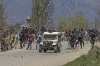 Kashmiri villagers throw stones and bricks at a police vehicle during a protest near the site of a gunbattle in Pulwama, south of Srinagar, Indian controlled Kashmir, Friday, April 2, 2021. Anti-India protests and clashes have erupted between government forces and locals who thronged a village in disputed Kashmir following a gunbattle that killed three suspected militants. Police say the gunfight on Friday erupted shortly after scores of counterinsurgency police and soldiers launched an operation based on tip about presence of militants in a village in southern Pulwama district. (AP Photo/ Dar Yasin)