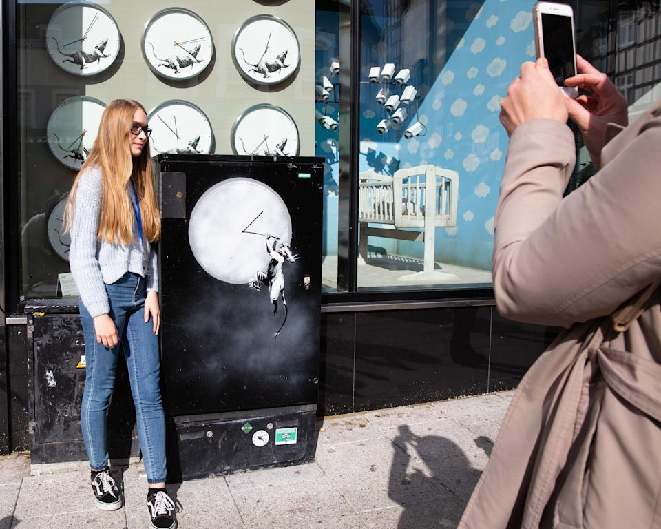 A member of the public has her picture taken outside Gross Domestic Product, a homeware store that is being launched in South London by the graffiti artist Banksy.