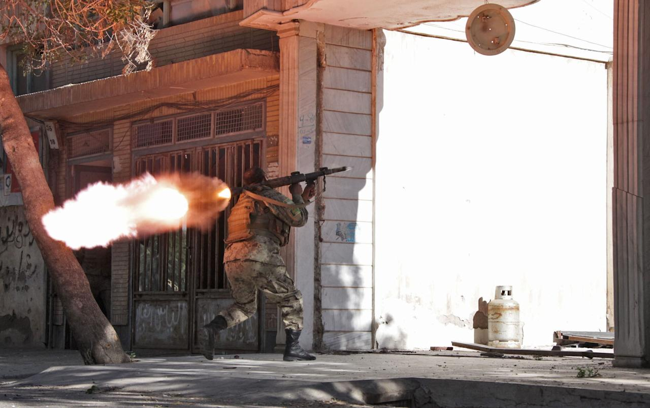 An Afghanistan's National Army (ANA) soldier fires his weapon at the site of a clash between insurgents and security forces over Indian Consulate in Herat, Afghanistan, Friday, May 23, 2014. Gunmen armed with machine guns and rocket-propelled grenades attacked the Indian Consulate in western Afghanistan's Herat province Friday, an assault that injured no diplomatic staff, police said. Indian officials said there had been a threat against its diplomats in Afghanistan, but gave no other details. (AP Photo/Hoshang Hashimi)