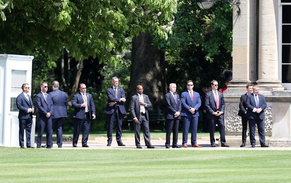 Always watching: President Trump\s' extensive security detail keep a close eye on proceedings at Buckingham Palace. (Chris Jackson/Getty Images)