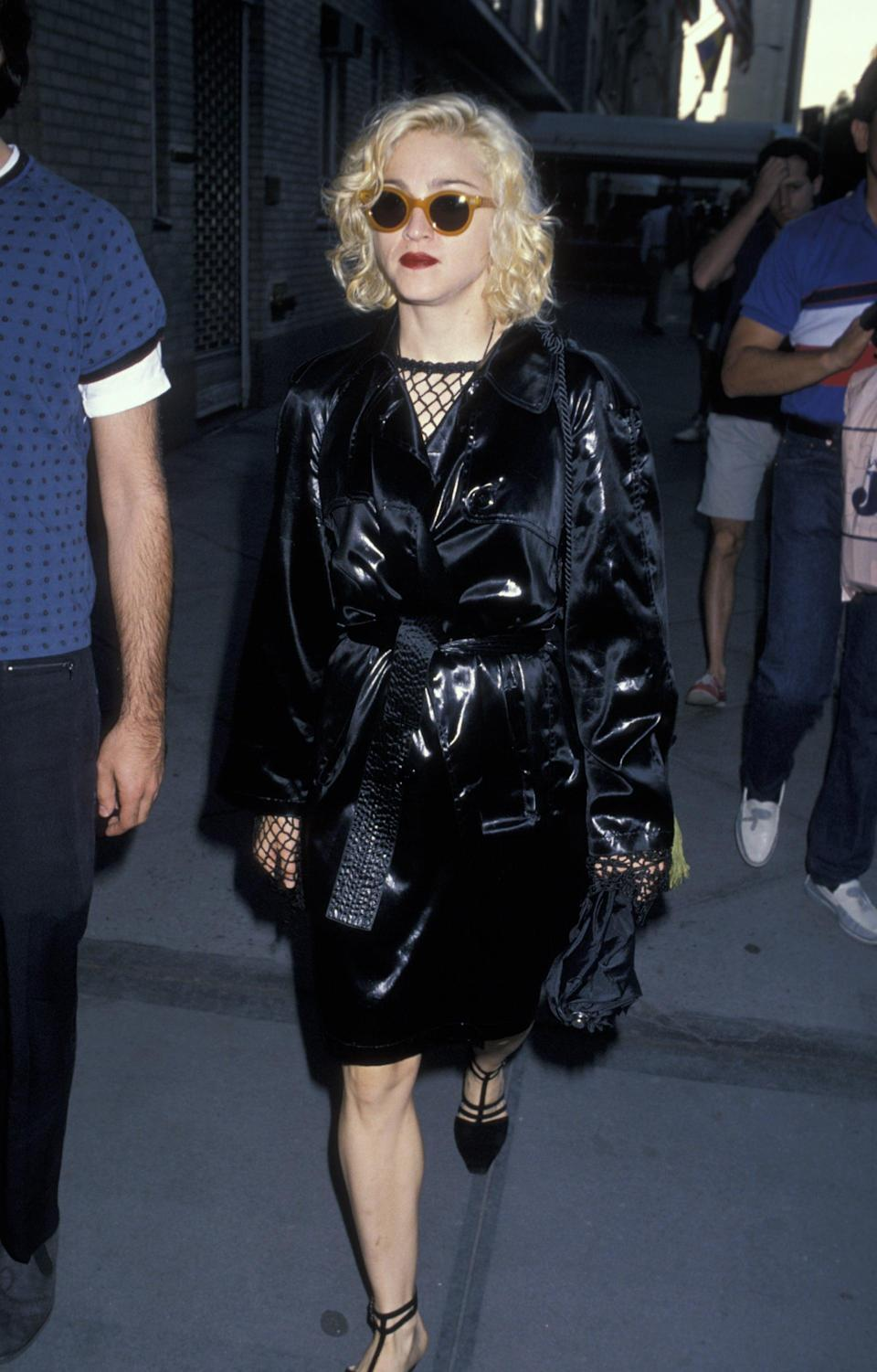"""<p><a href=""""https://www.popsugar.com/celebrity/Madonna-Costume-Ideas-45229957"""" class=""""link rapid-noclick-resp"""" rel=""""nofollow noopener"""" target=""""_blank"""" data-ylk=""""slk:Madonna"""">Madonna</a> infamously passed by the Plaza Hotel in New York wearing this stylish black outfit like a true material girl. Here, she played around with textures, contrasting fishnet details with a shiny vinyl jacket. To top it off, effortless brown, round sunglasses and a dark red lip gave her look a pop of color. </p>"""