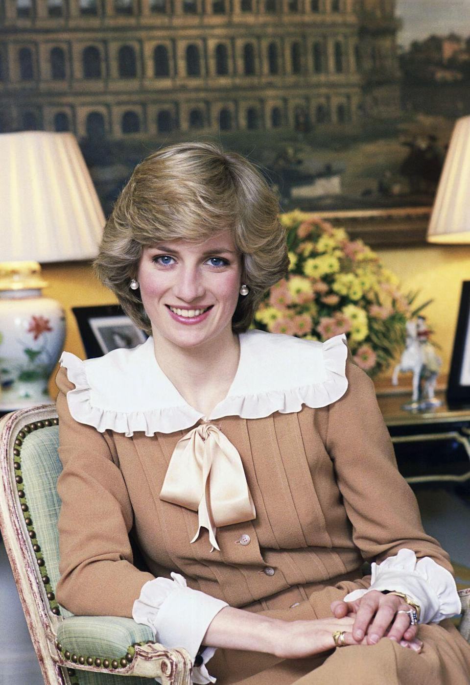 <p>The Princess of Wales at Kensington Palace in February 1983 wearing a camel dress with a 1930's style wide collar complete with ruffles and a bow.</p>
