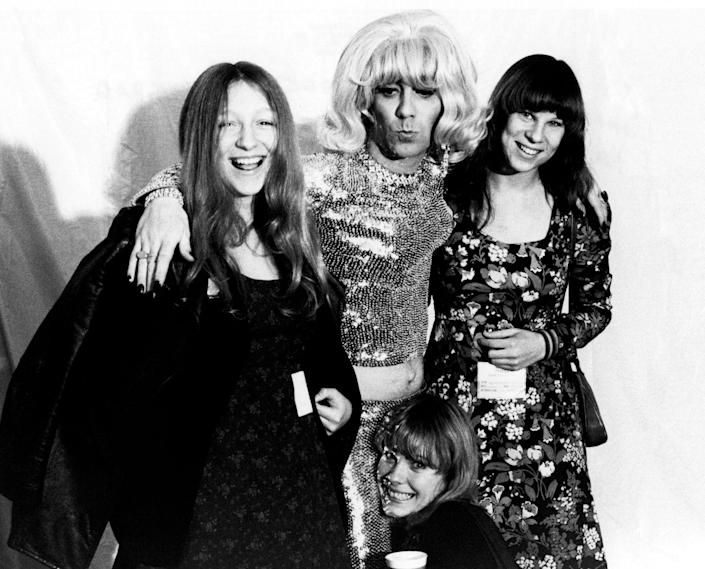 <p>The Who drummer, Keith Moon, poses with fans while dressed in a blonde wig and sequin outfit backstage at a concert in 1972. </p>