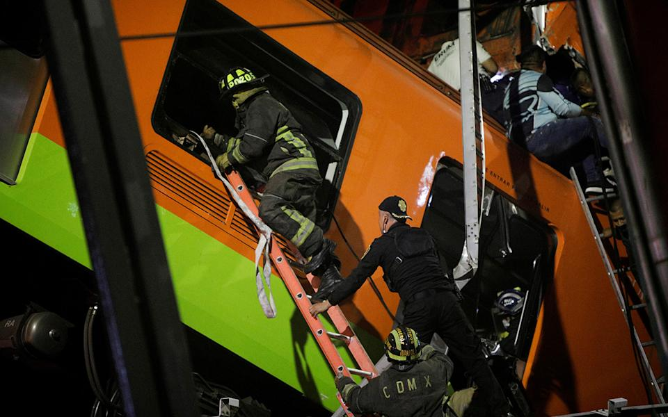 Rescuers work at a site where an overpass for a metro partially collapsed with train cars on it.