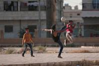 Youths play soccer on a street in Manbij, in Aleppo Governorate, Syria, August 9, 2016. REUTERS/Rodi Said