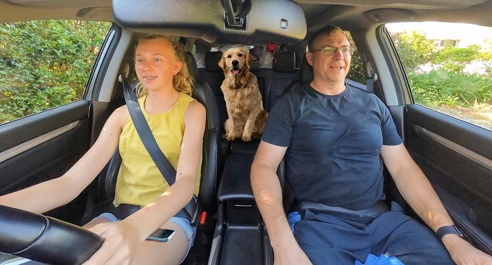 Two people are pictured in a car with a dog in the backseat.