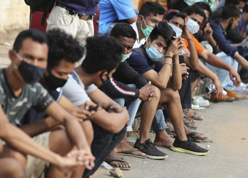 Stranded migrant workers wait to board buses before taking a special train to their destination during extended lockdown to curb the spread of new coronavirus, in Bangalore, India, Monday, May 18, 2020. India has recorded its biggest single-day surge in new cases of coronavirus. The surge in infections comes a day after the federal government extended a nationwide lockdown to May 31 but eased some restrictions to restore economic activity and gave states more control in deciding the nature of the lockdown. (AP Photo/Aijaz Rahi)