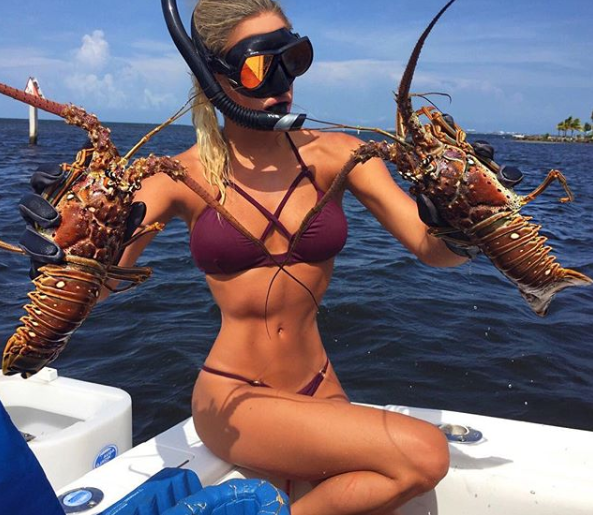 A photo of the 'World's sexiest extreme fisher' Emily Reimer wearing a blue bikini on a boat with two crayfish.
