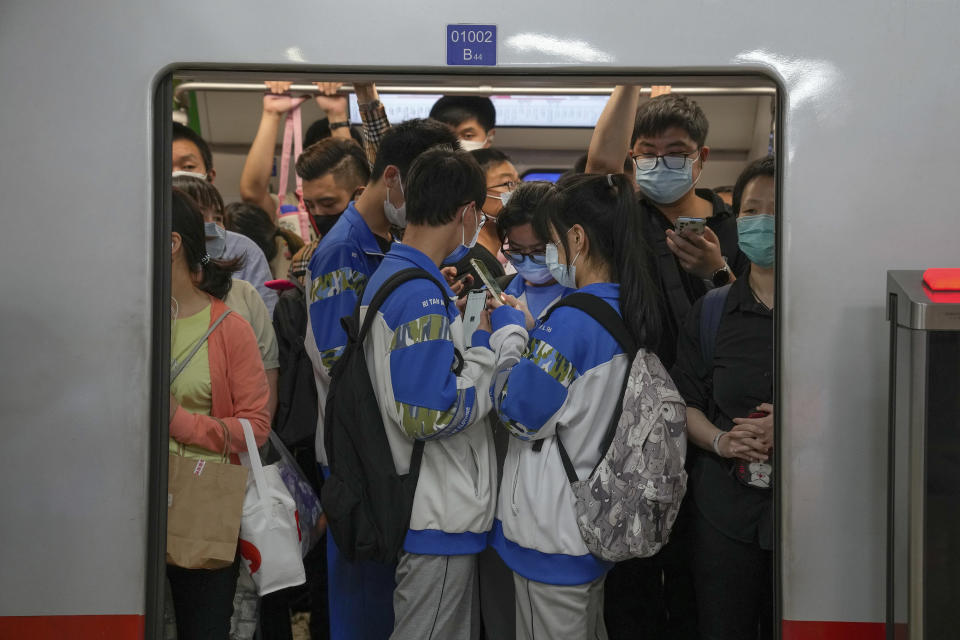 Students browsing their smartphones crowd with commuters inside a subway train in Beijing Tuesday, Sept. 14, 2021. China has set new rules limiting the amount of time kids can spend playing online games. (AP Photo/Andy Wong)